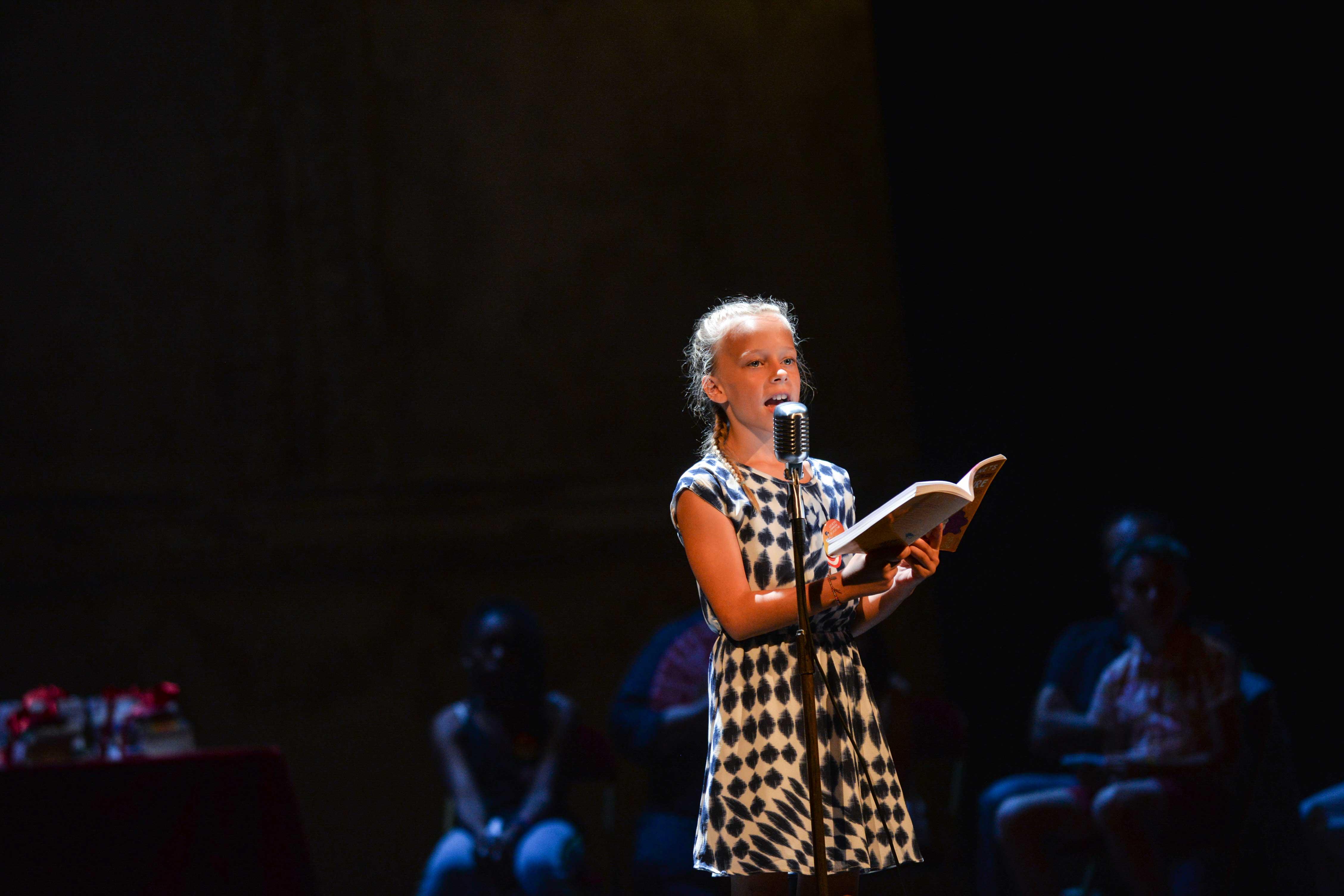 Photo d'Éléonore en pleine lecture sur scène 2018