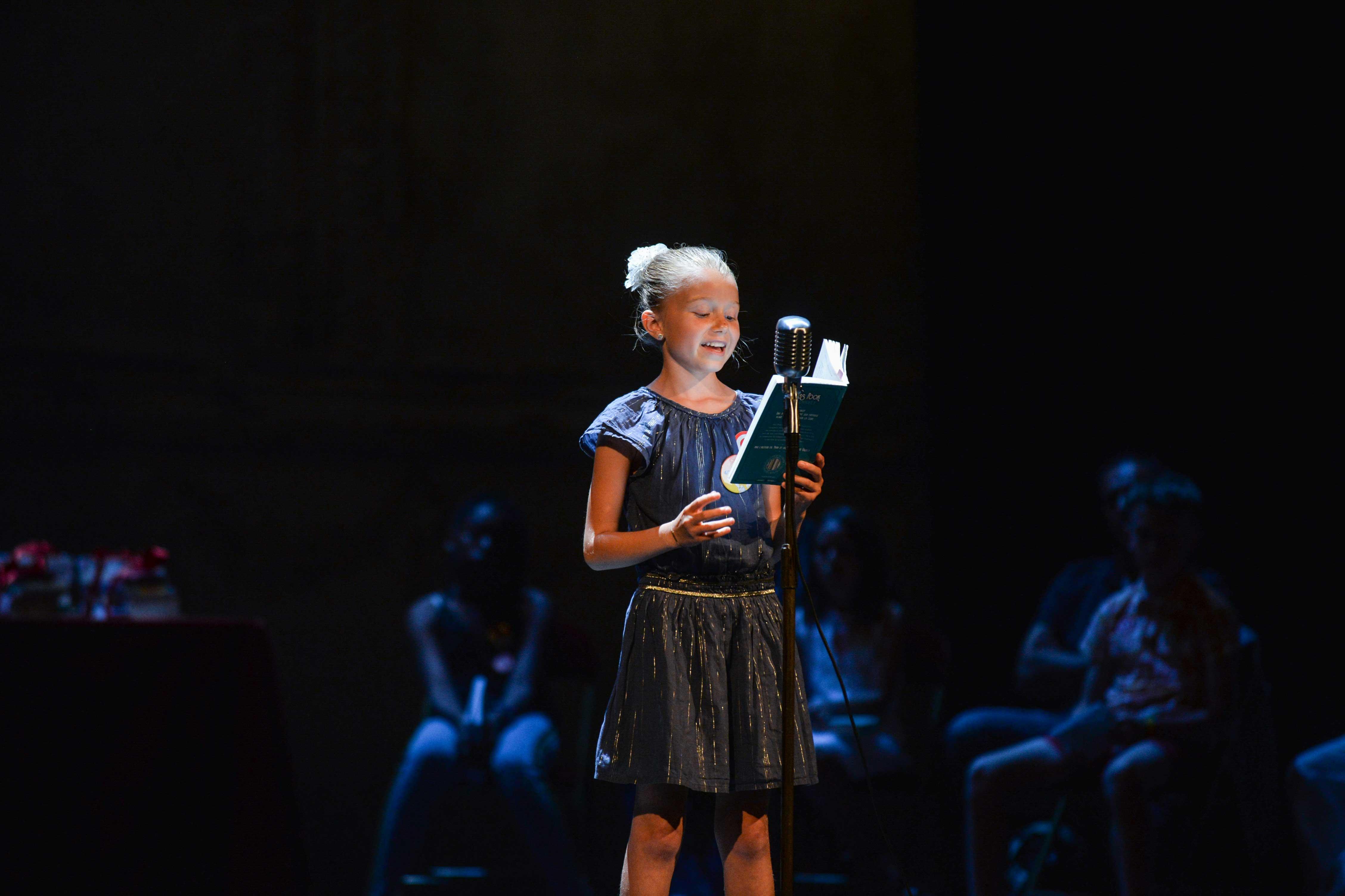 Photo d'Élise en pleine lecture sur scène 2018
