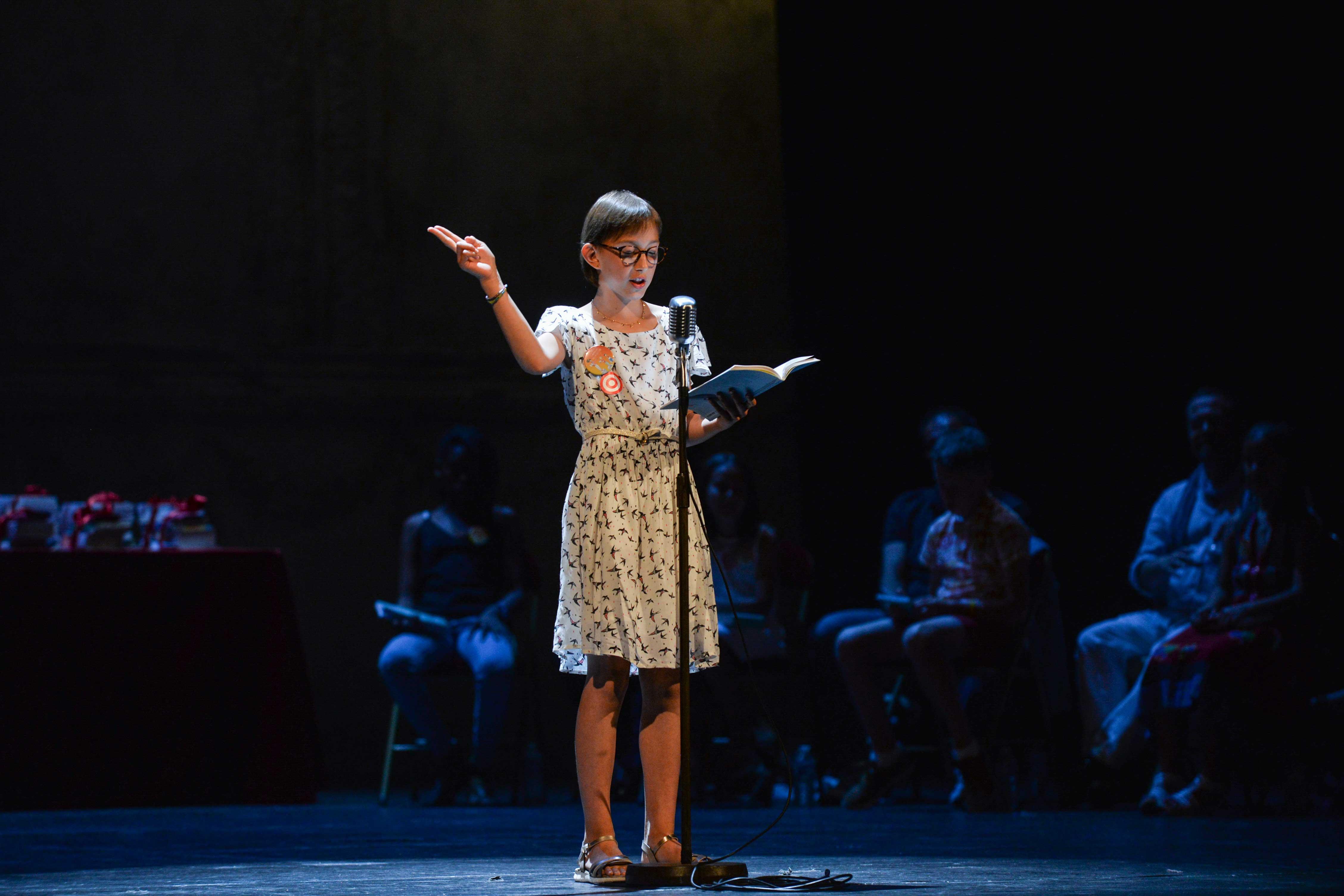 Photo d'Éloise en pleine lecture sur scène 2018