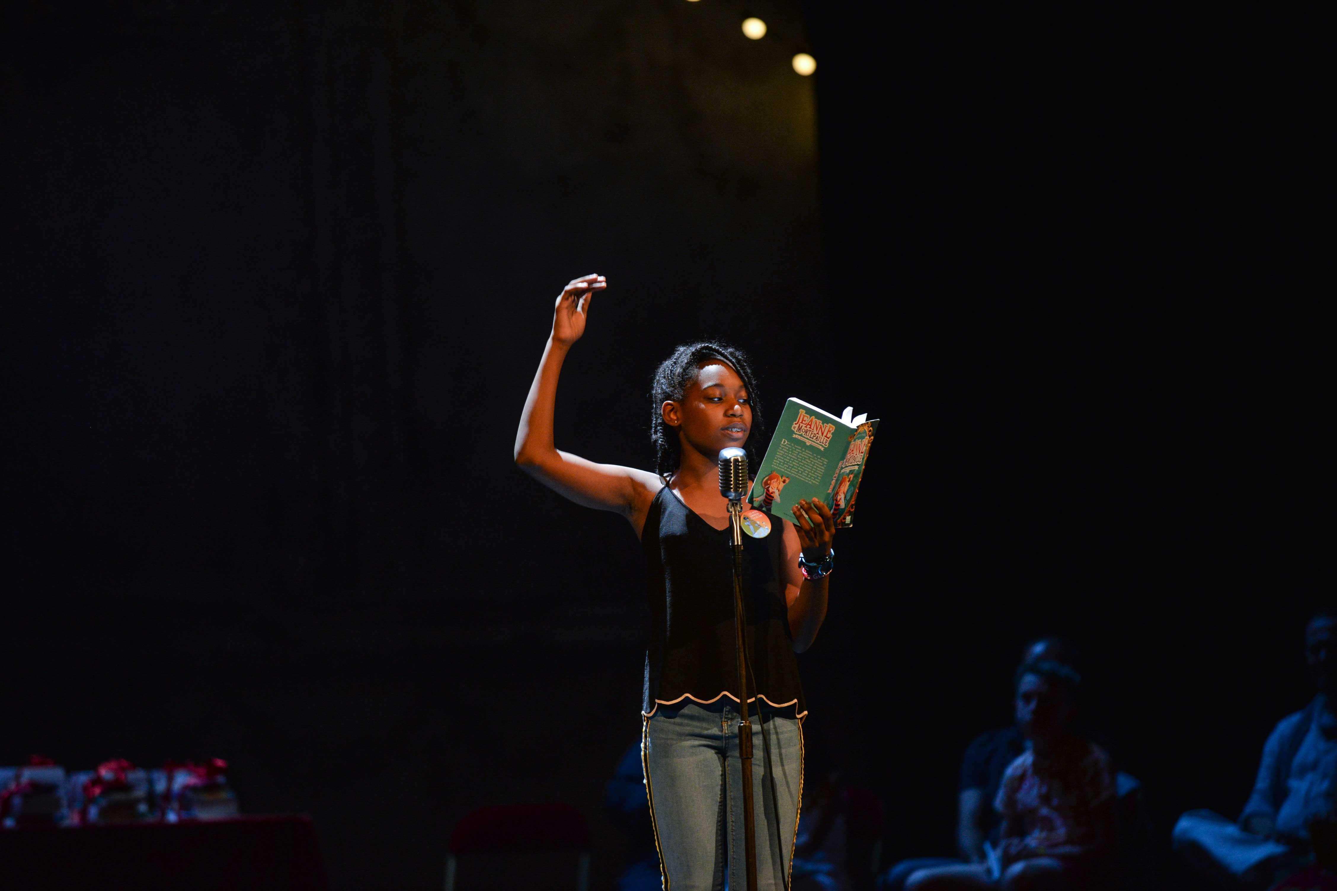 Photo de Janel en pleine lecture sur scène 2018