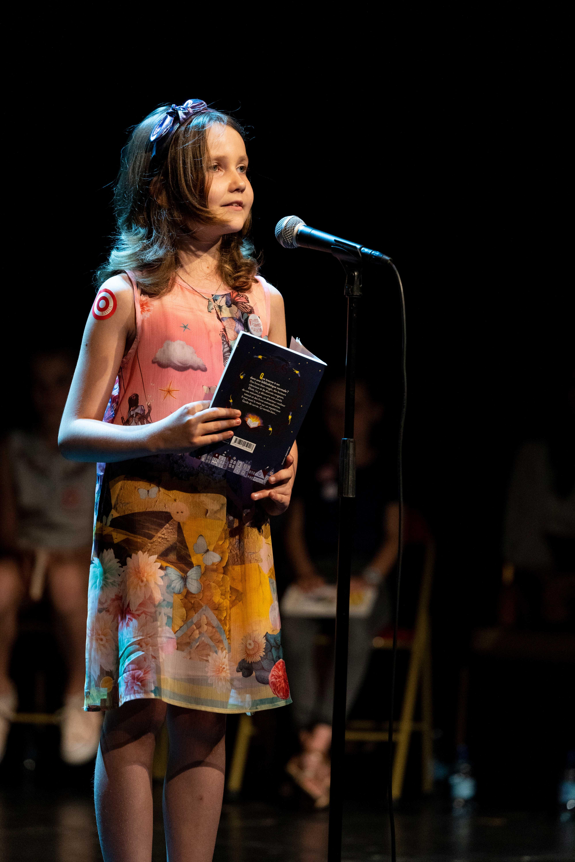 Photo de Leila en pleine lecture sur scène 2019