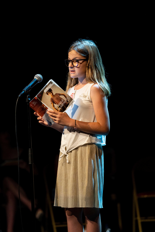 Photo de Lily en pleine lecture sur scène 2019