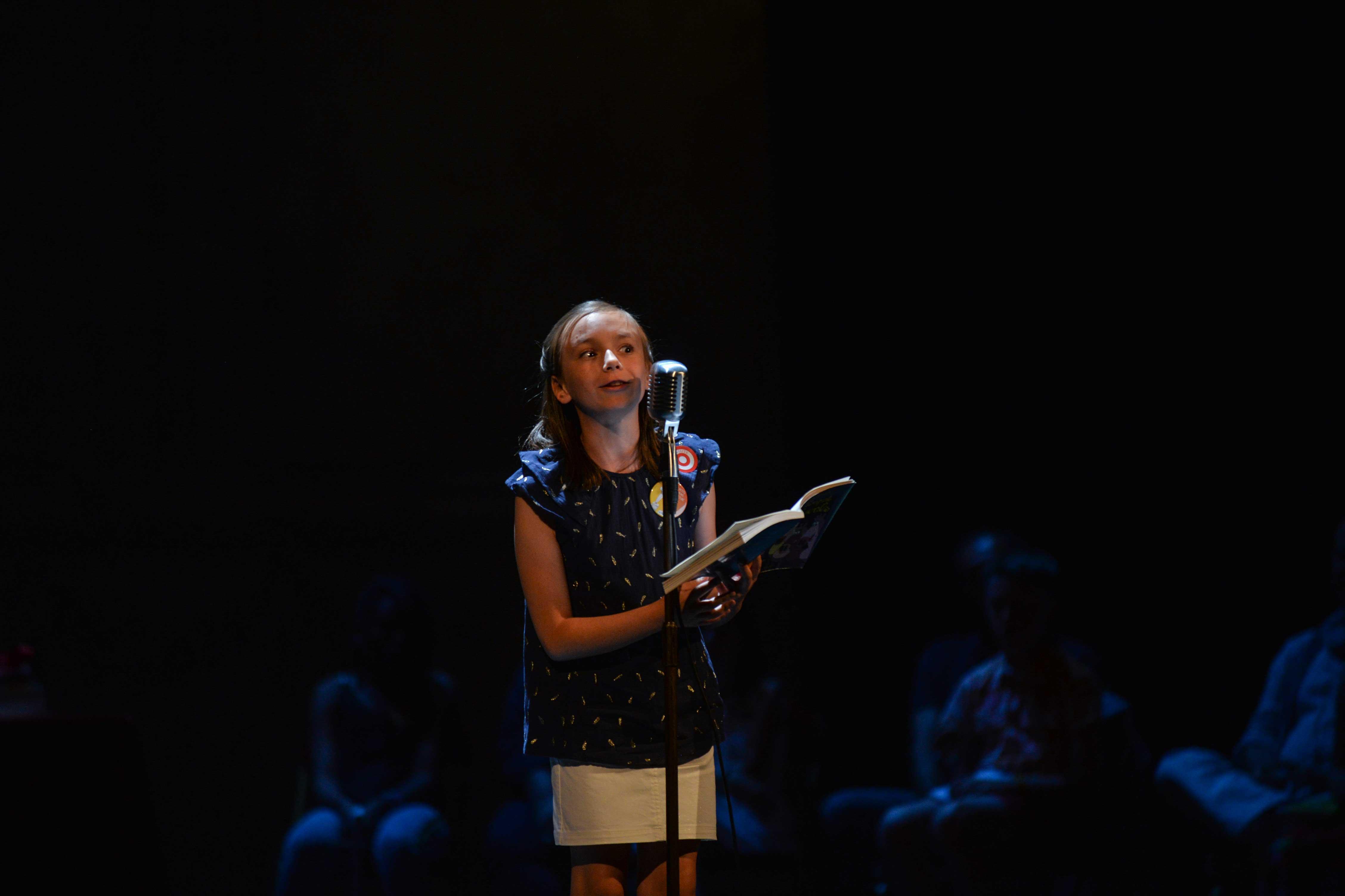 Photo de Sixtine en pleine lecture sur scène 2018