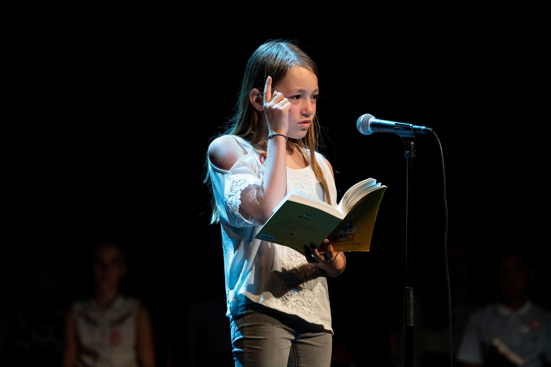Photo de Yana en pleine lecture sur scène 2019